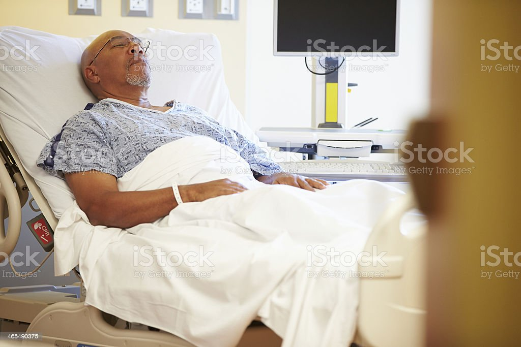 Senior Male Patient Resting In Hospital Bed stock photo