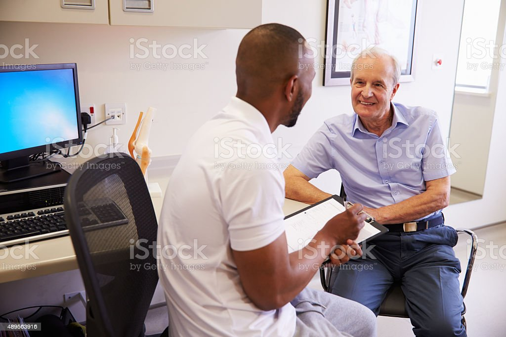 Senior Male Patient Working With Physiotherapist In Hospital stock photo