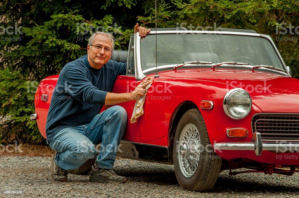 Senior Male Polishing a Vintage Sports Car stock photo