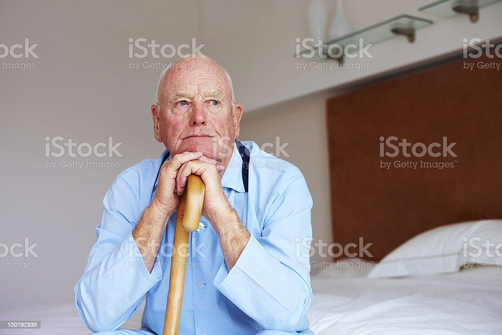 Senior male resting hands and chin on walking cane stock photo