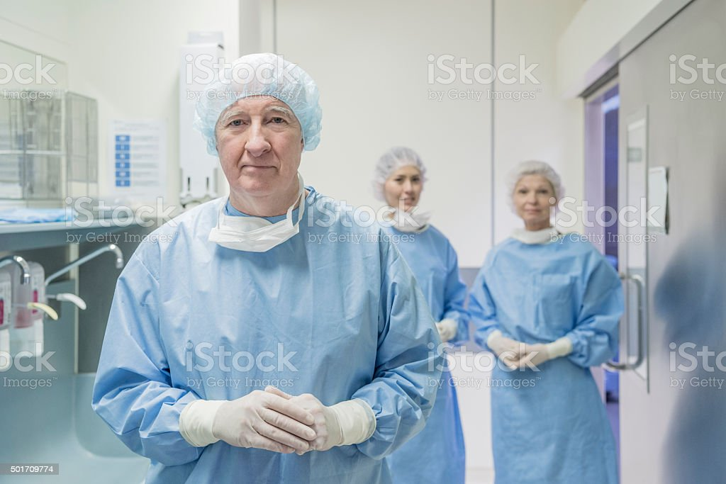 Senior male surgeon wearing scrubs and surgical cap in hospital stock photo