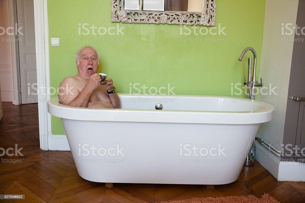senior male surprised in bath in bedroom stock photo