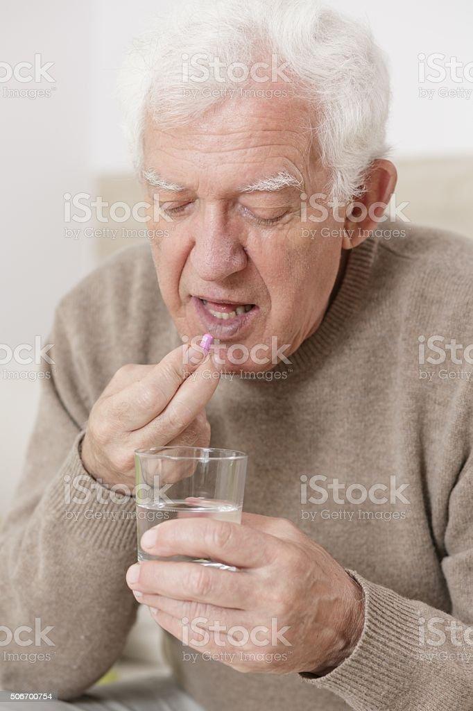 Senior male taking pill stock photo