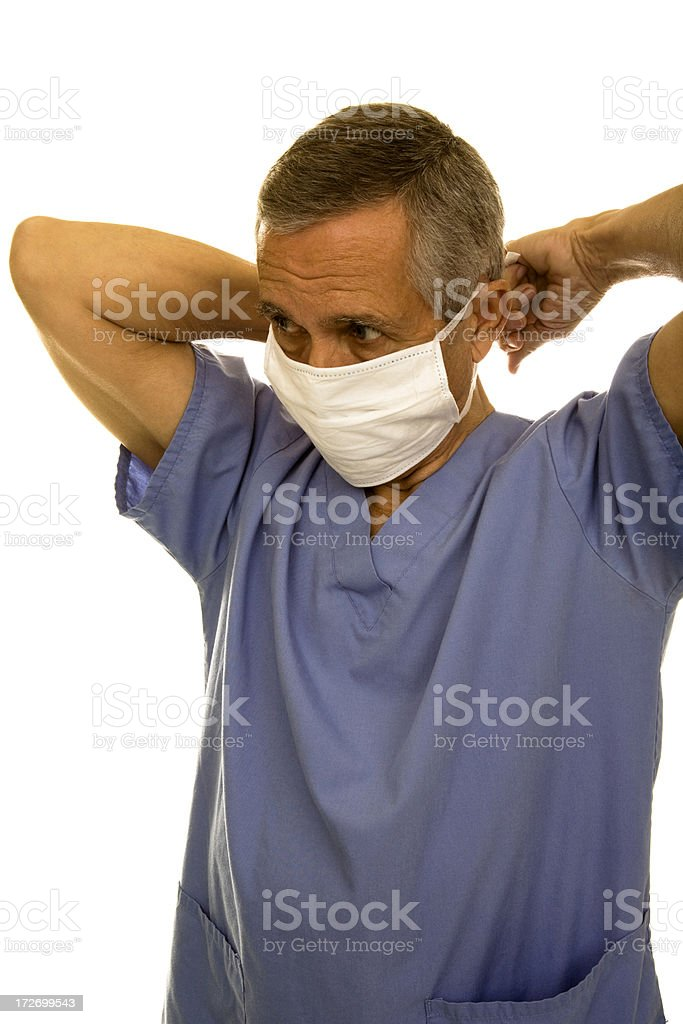 Senior male wearing scrubs and putting on surgical mask royalty-free stock photo