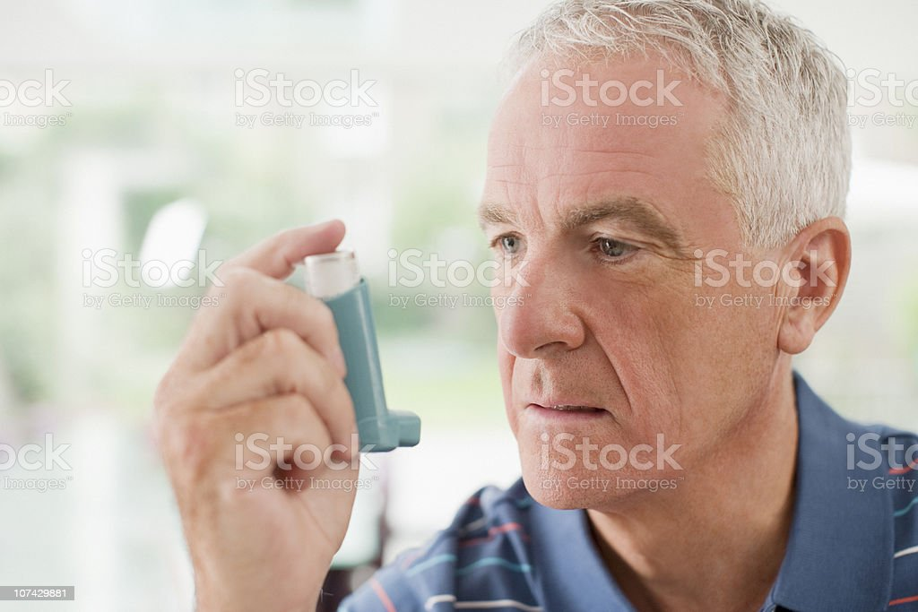 Senior man about to use asthma inhaler stock photo