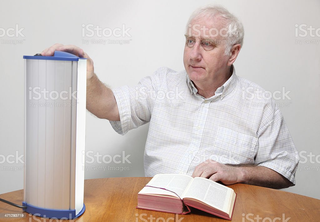 senior man adjusts seasonal affective disorder SAD lamp stock photo