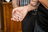 Senior Man and a Caregiver Holding Hands