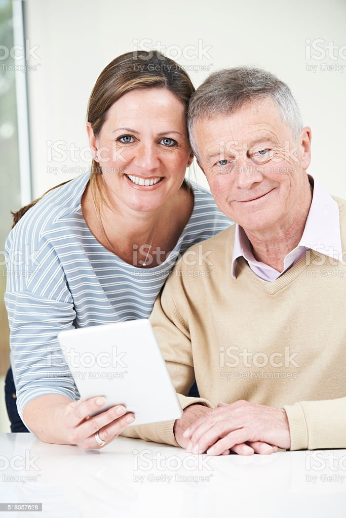 Senior Man And Adult Daughter Looking At Digital Tablet Together stock photo