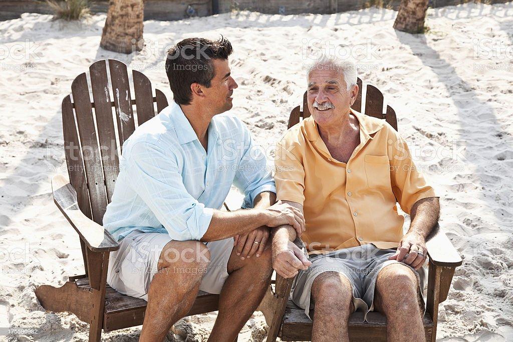Senior man and adult son at beach royalty-free stock photo
