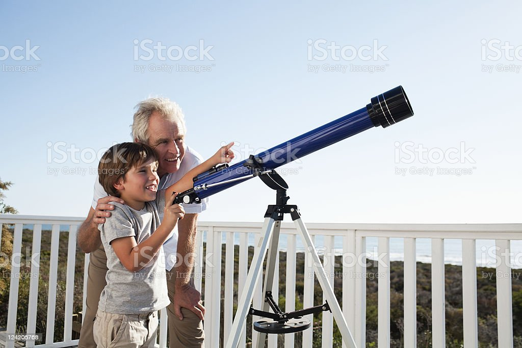 Senior man and boy with a telescope stock photo