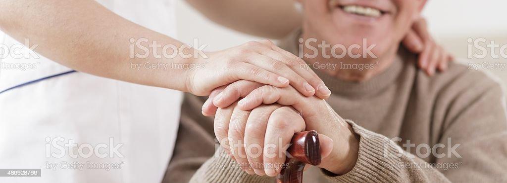 Senior man and caring nurse stock photo