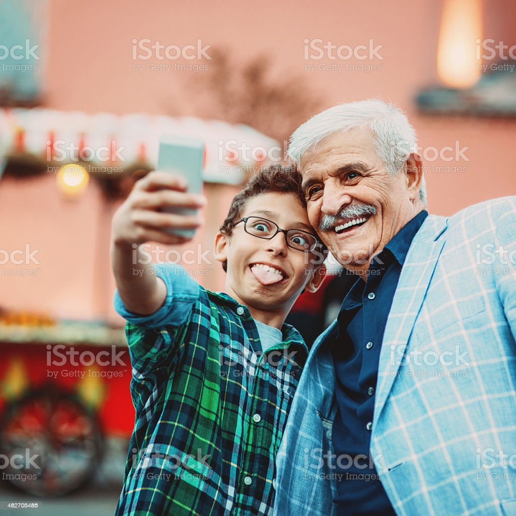 Senior man and little boy making selfie stock photo