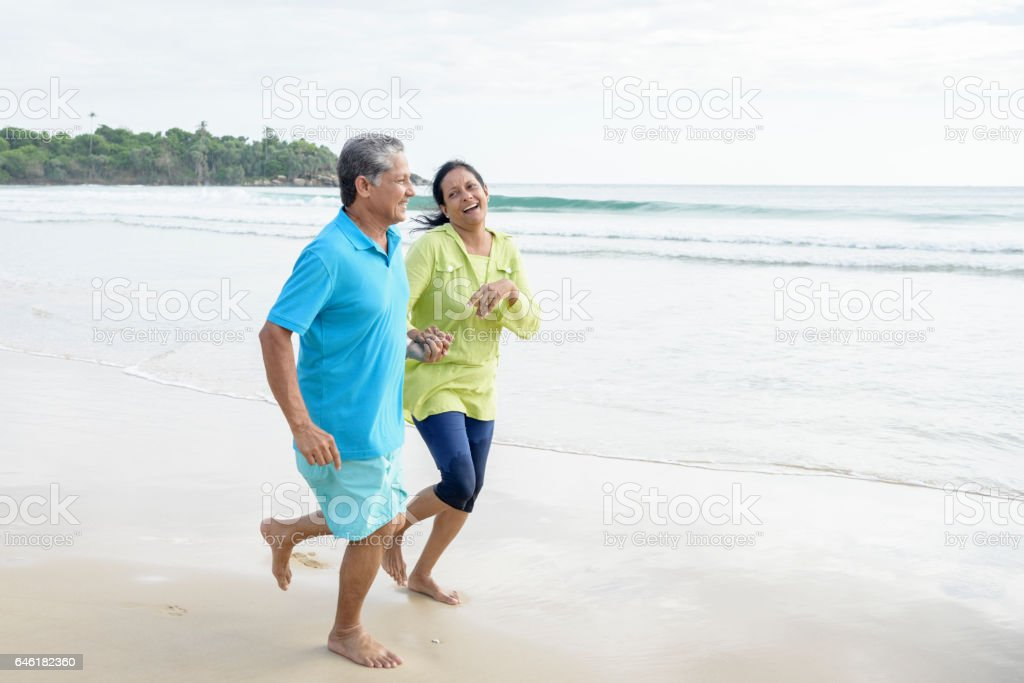 Couple smiling on vacation holding hands and running at the sea shore