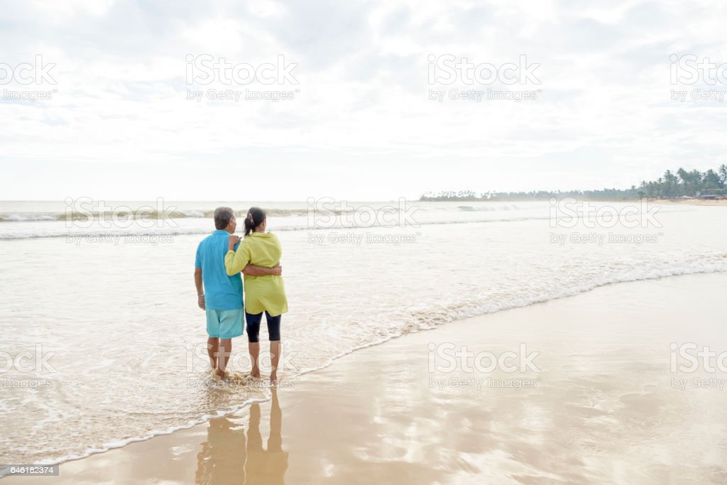 Senior man and mature woman on beach with arm around each other stock photo