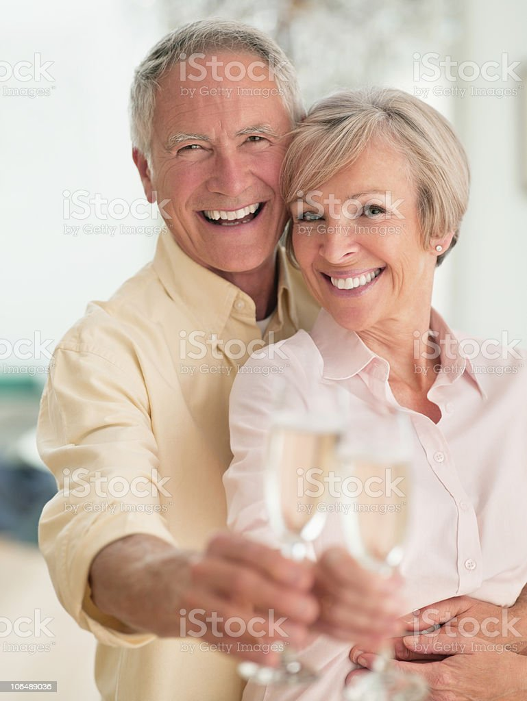 Senior man and mature woman toasting glass of wine royalty-free stock photo