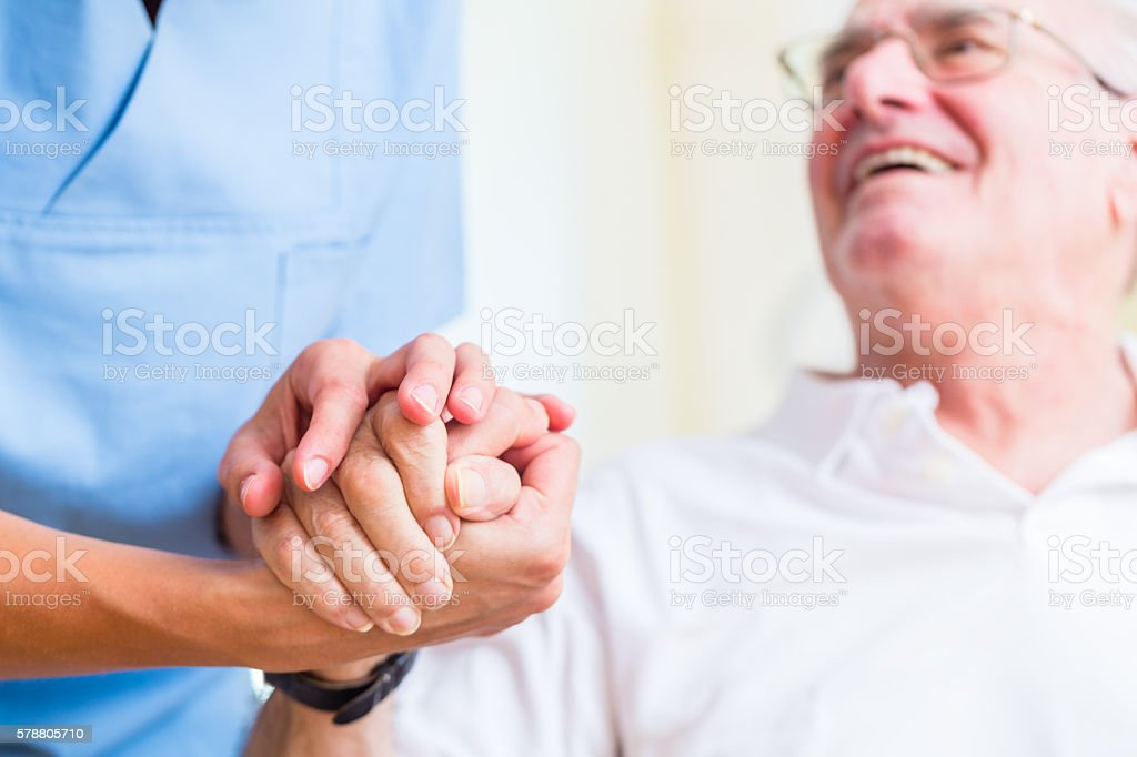 Senior man and old age nurse in nursing home stock photo