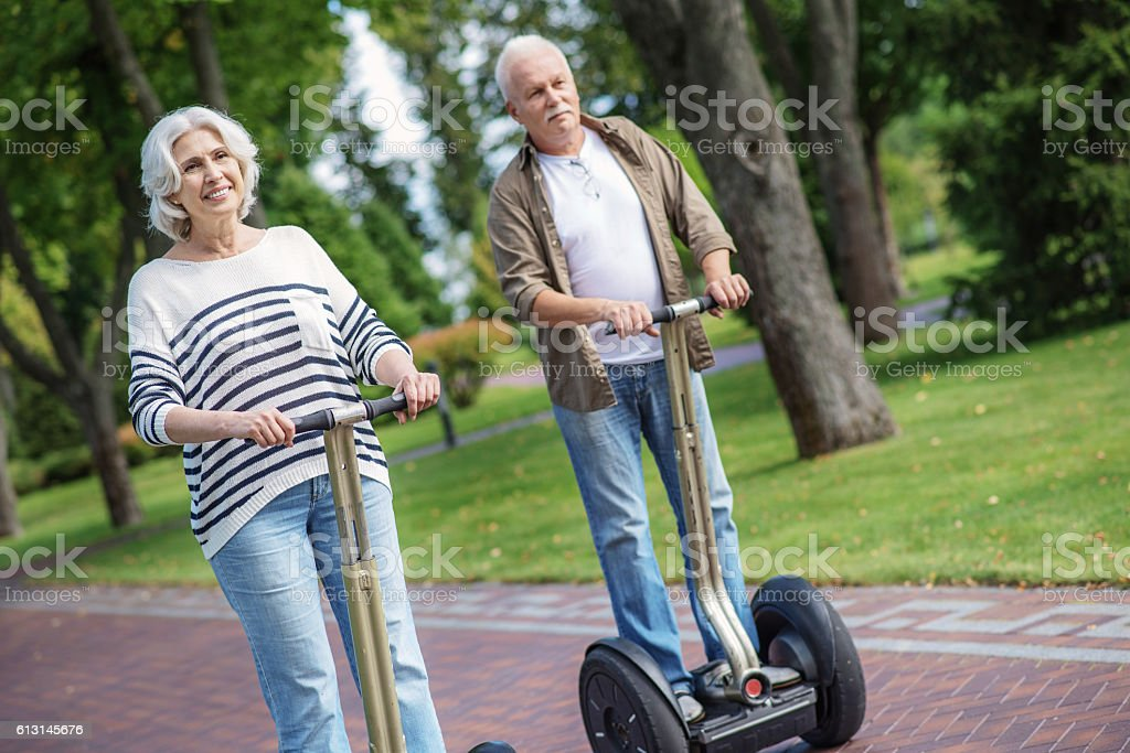 Senior man and woman driving modern transport stock photo