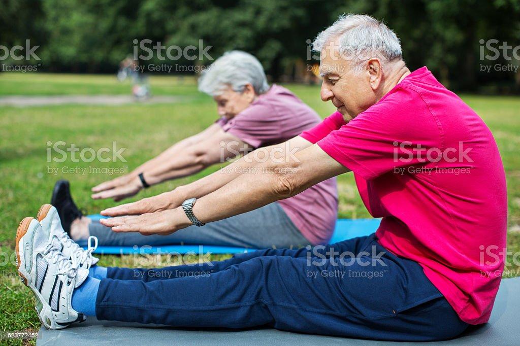 Senior man and woman exercising at the park stock photo