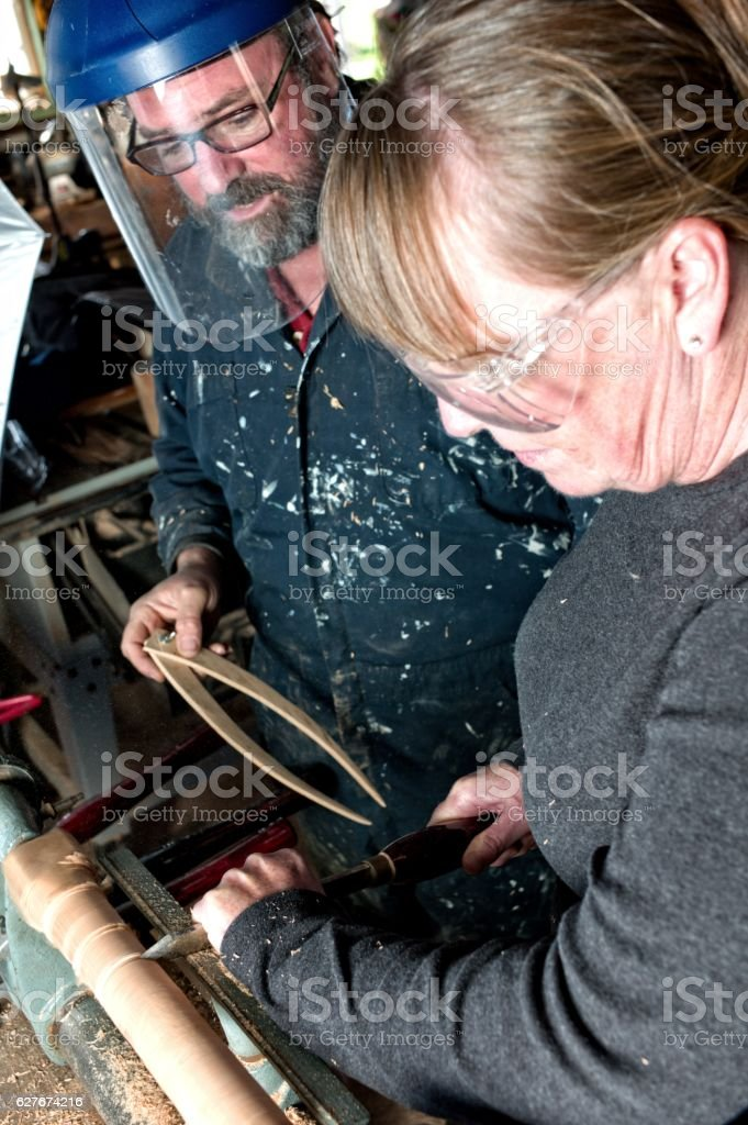 Senior man and woman teaching wood lathe in wood shop. stock photo