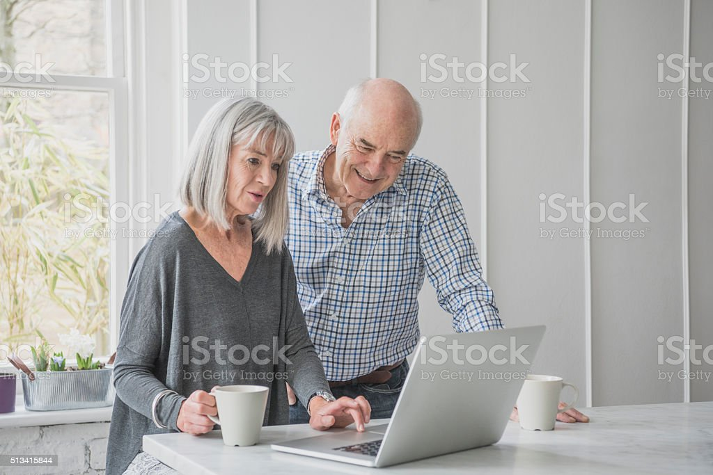 Senior man and woman with laptop and coffee stock photo