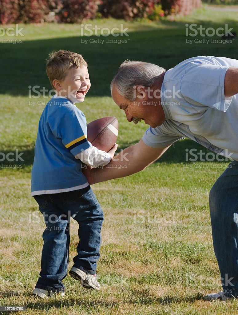 Senior man and young boy enjoying life playing football royalty-free stock photo