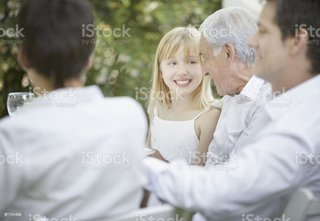 Senior man and young girl embracing and smiling at outdoor party with people around them royalty-free stock photo