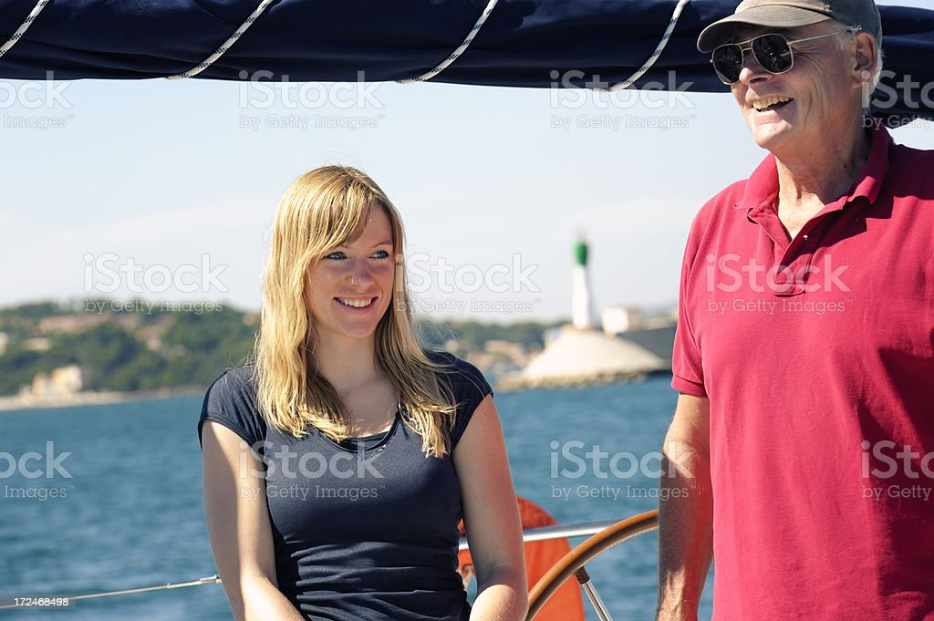 Senior Man and Young Woman Aboard Sailing Yacht royalty-free stock photo