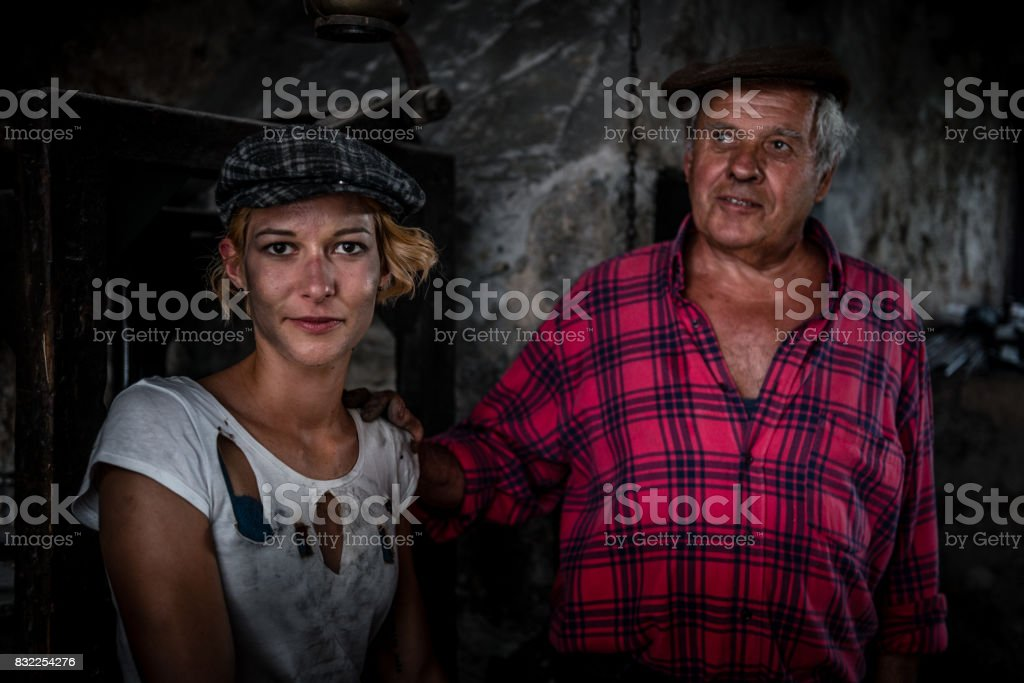 Senior Man and Young Woman in Blacksmith Shop stock photo