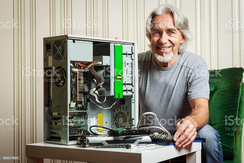 Senior man assembling a desktop computer stock photo