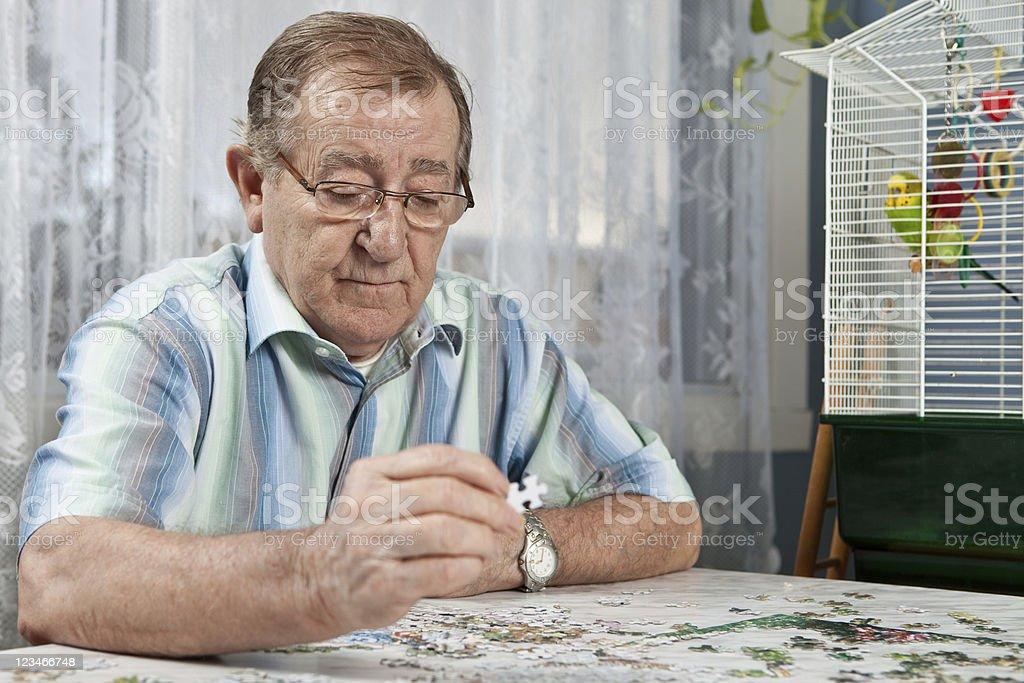 Senior man assembling a puzzle stock photo