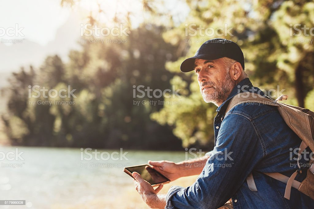 Senior man at a lake with backpack and digital tablet stock photo