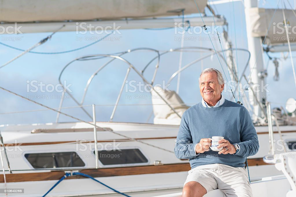 Senior man at boat dock on yacht drinking coffee stock photo