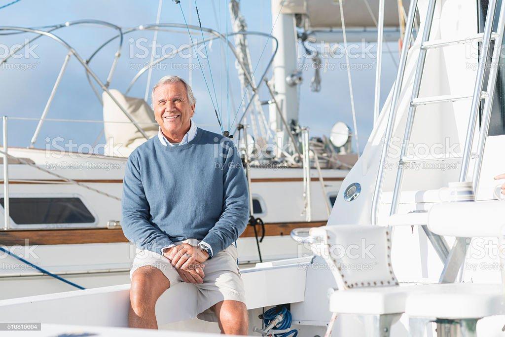 Senior man at boat dock sitting on yacht stock photo