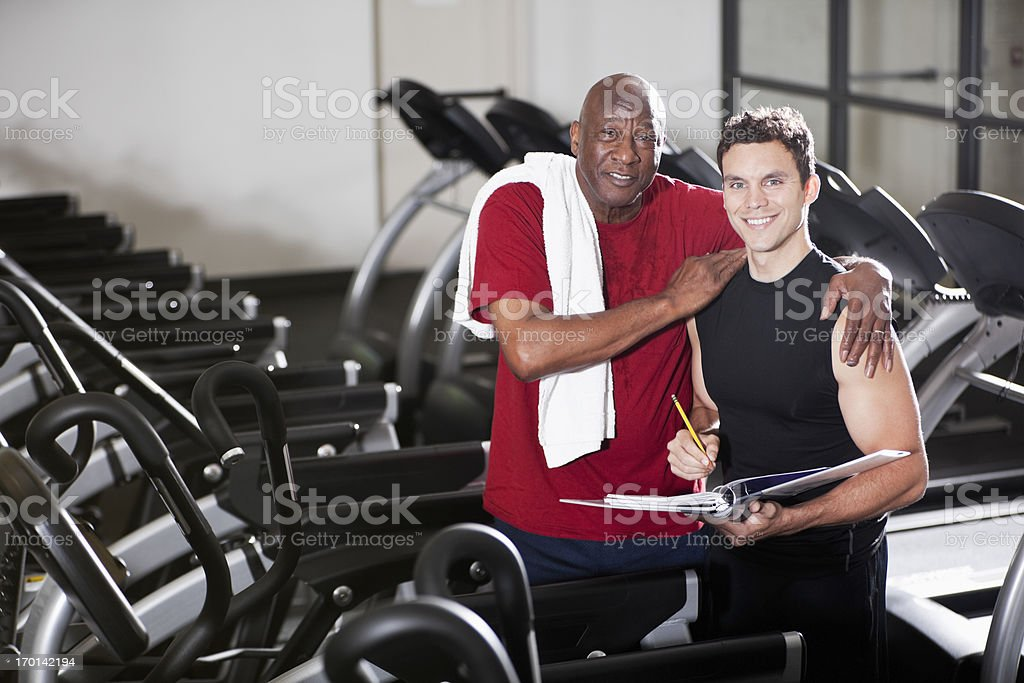 Senior man at health club with personal trainer stock photo