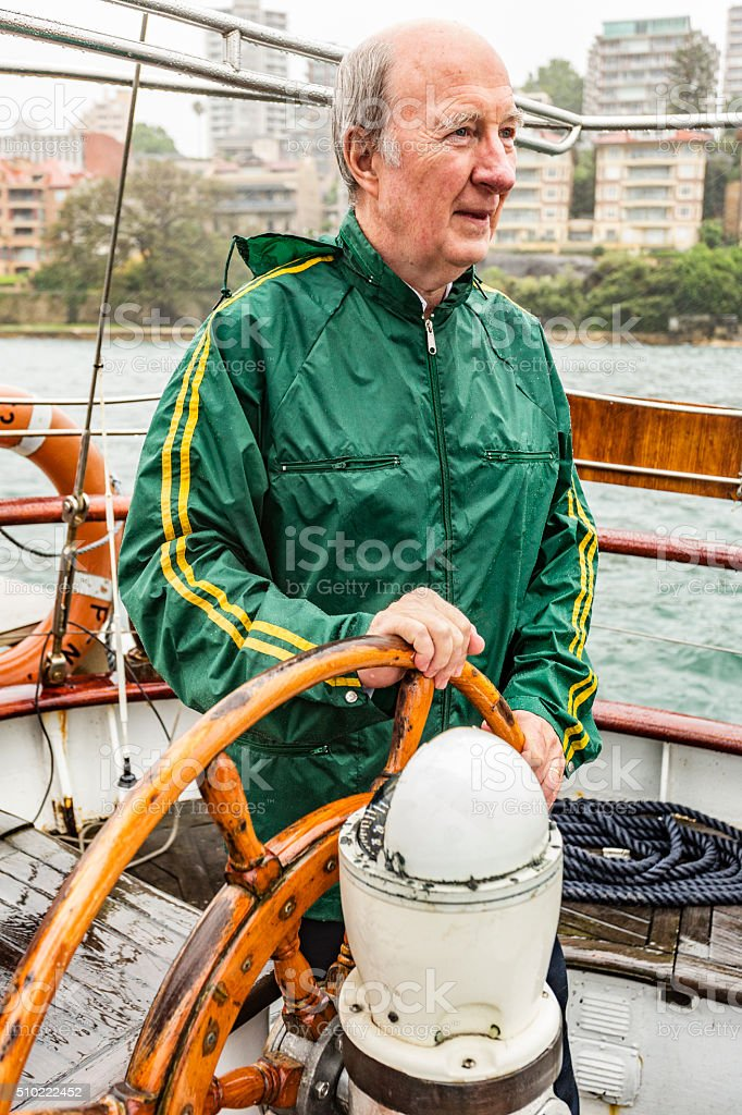 Senior Man At Helm of Yacht During a Sydney Storm stock photo