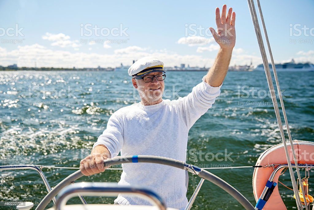 senior man at helm on sailing boat in sea stock photo