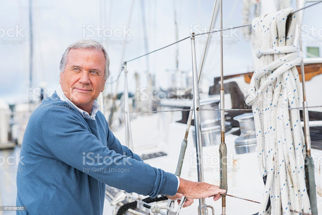 Senior man at marina, standing next to his yacht stock photo