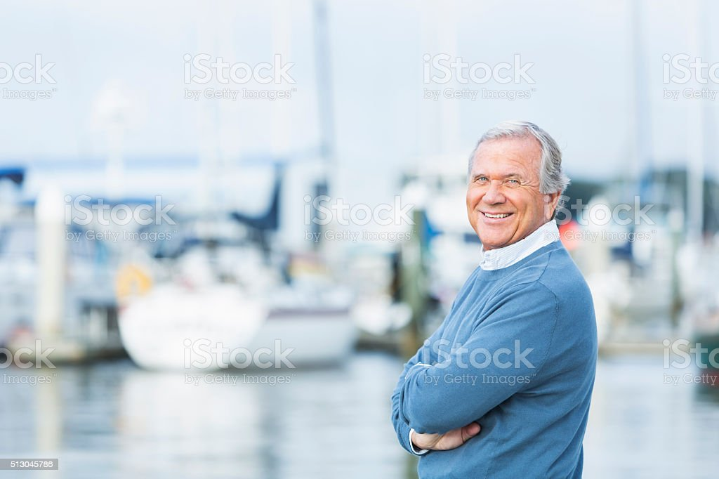 Senior man at marina, standing with arms folded stock photo