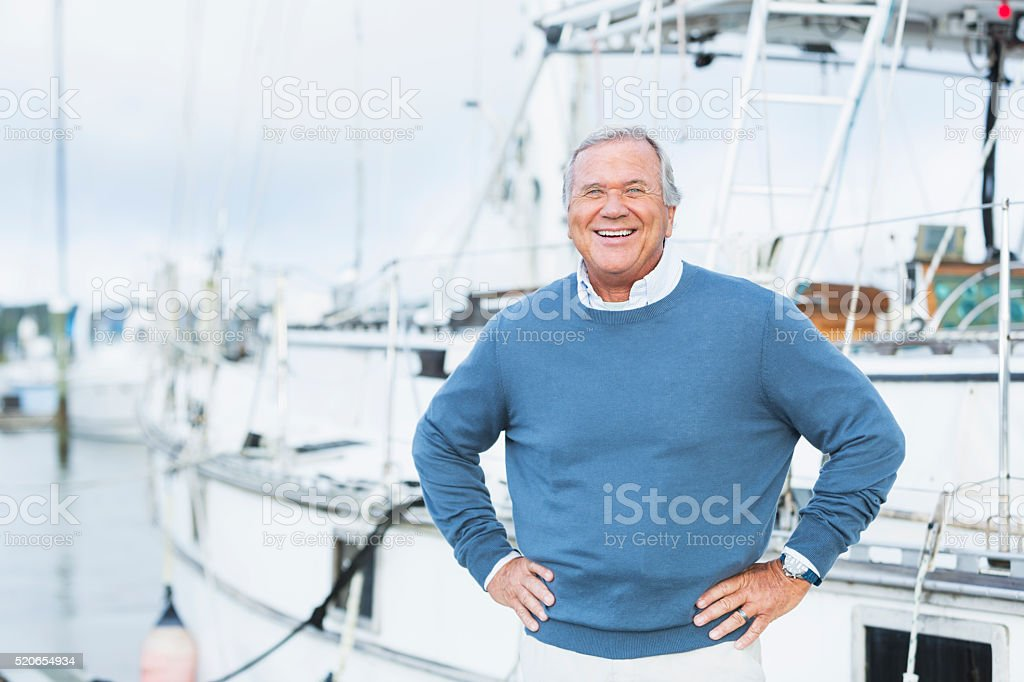 Senior man at marina, standing with hands on hips stock photo