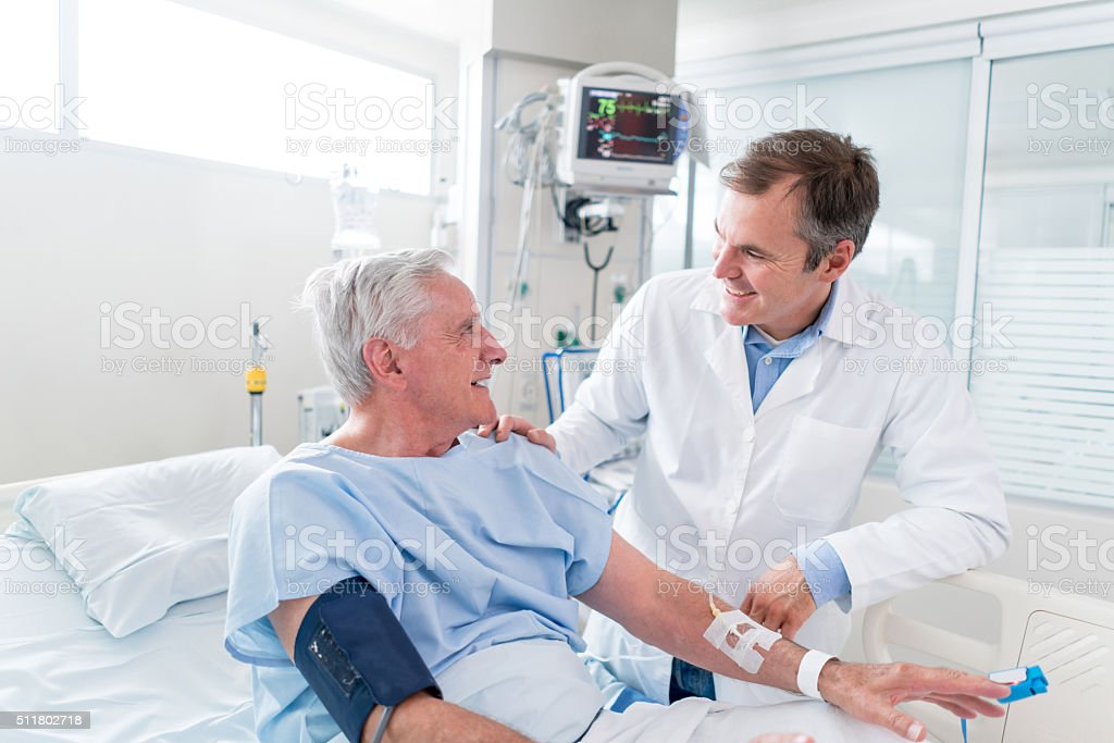 Senior man at the ICU talking to the doctor stock photo