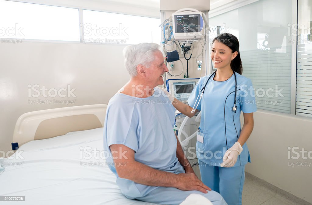 Senior man at the ICU talking to the nurse stock photo