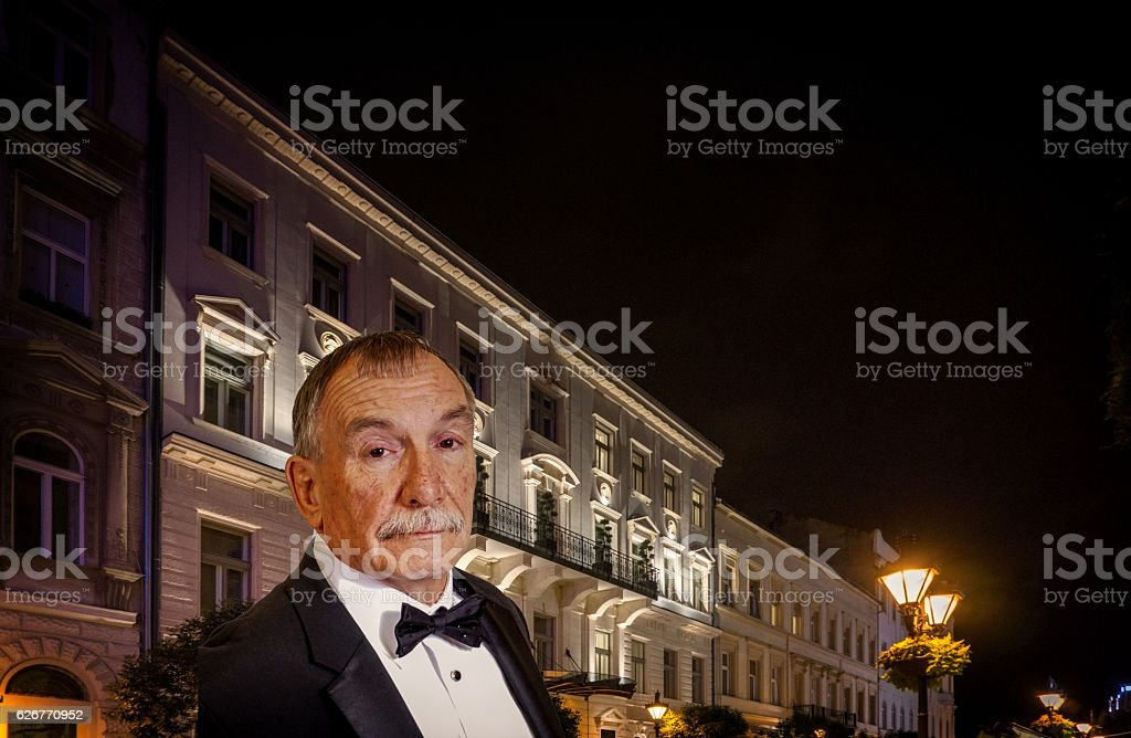 Senior man attending swish party in city at night stock photo