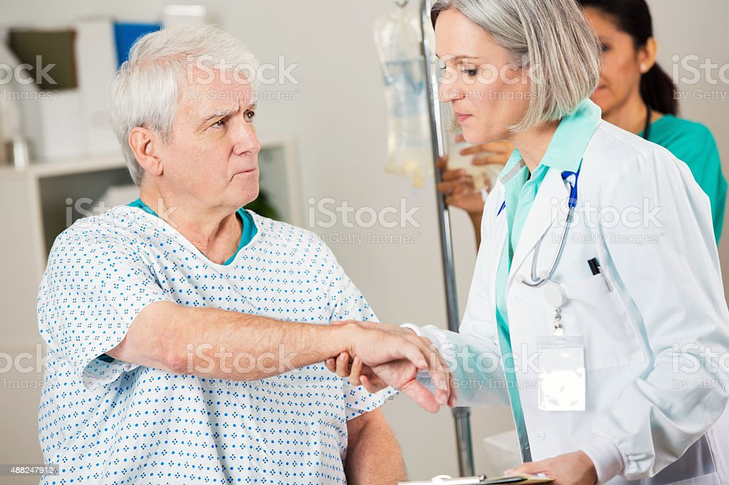 Senior man being examined by female doctor in hospital room stock photo