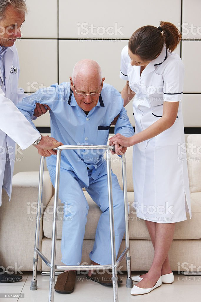 Senior Man Being Helped to a Walker royalty-free stock photo