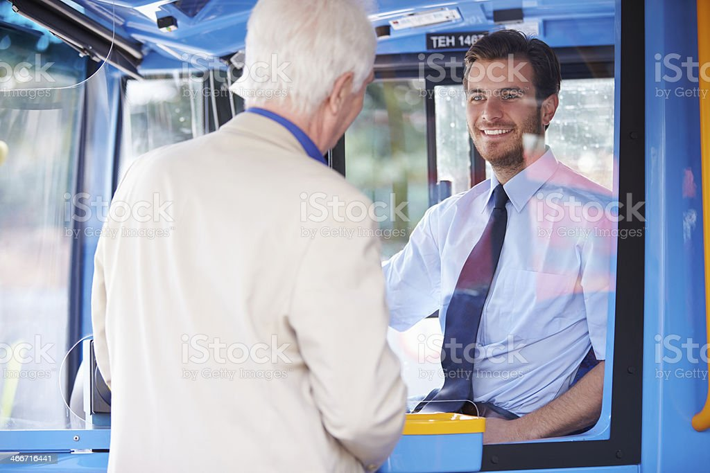 Senior Man Boarding Bus And Buying Ticket stock photo