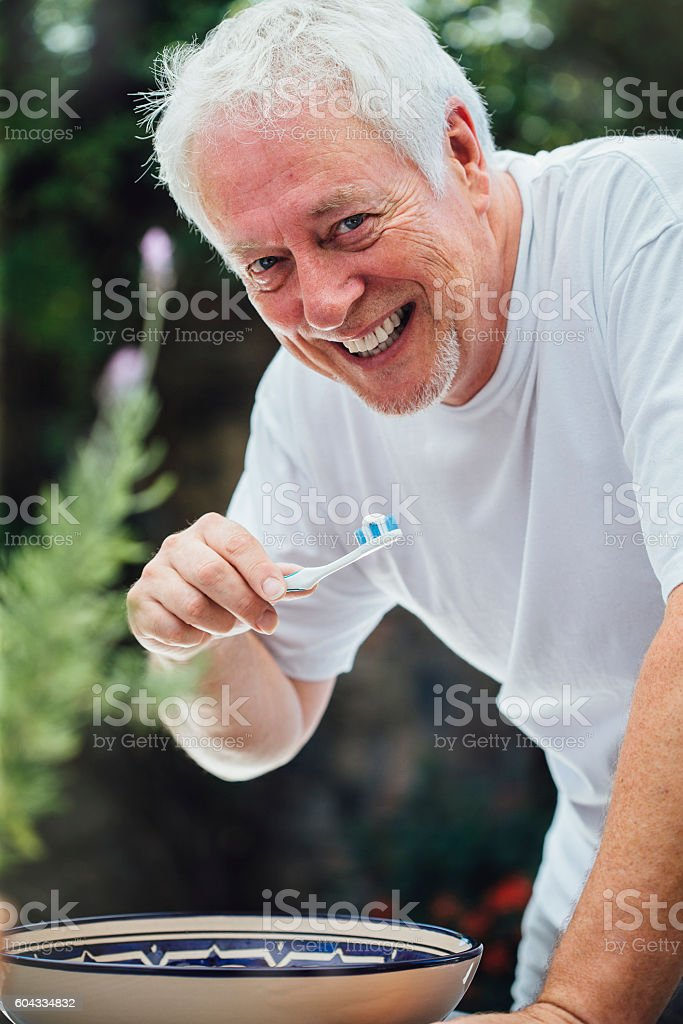 Senior Man Brushing Teeth Outdoors stock photo
