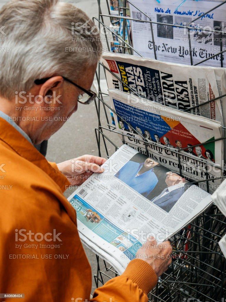 Senior man buy english press about United Kingdom general election of 2017 stock photo
