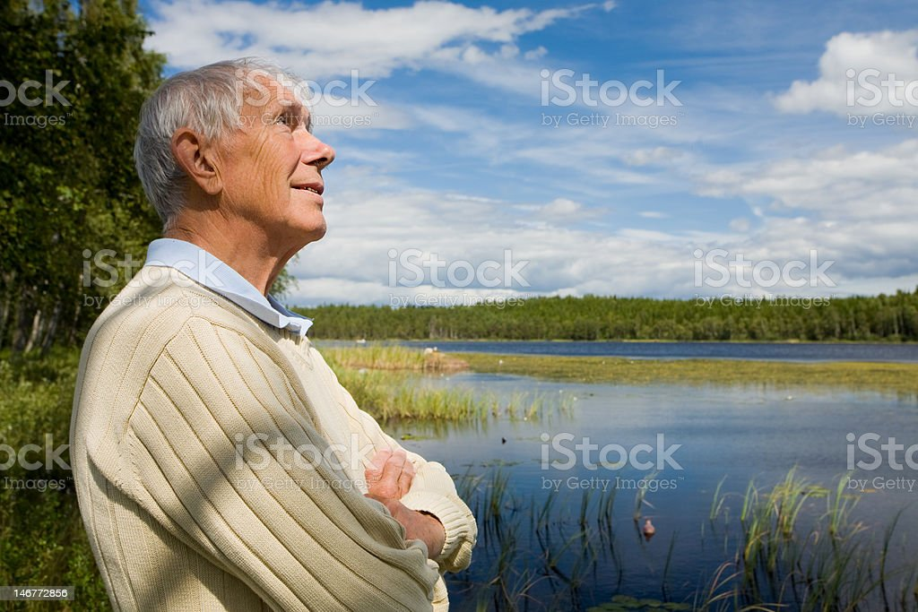 Senior man by a lakeside royalty-free stock photo