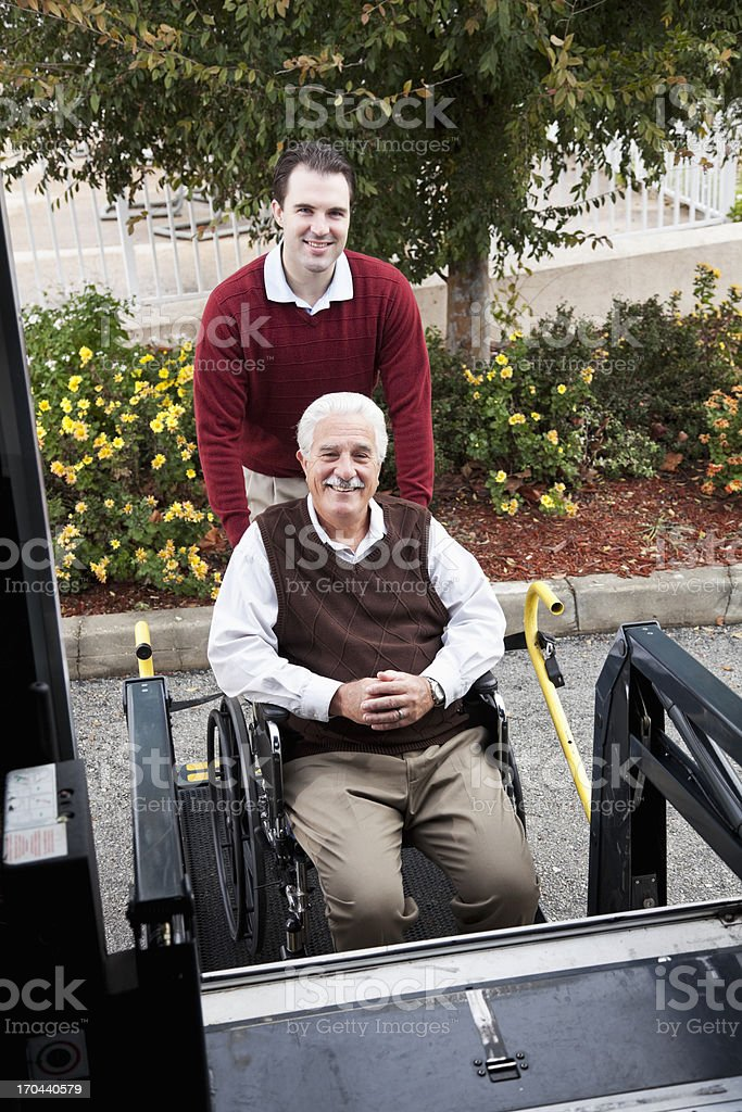 Senior man by minibus with wheelchair lift stock photo