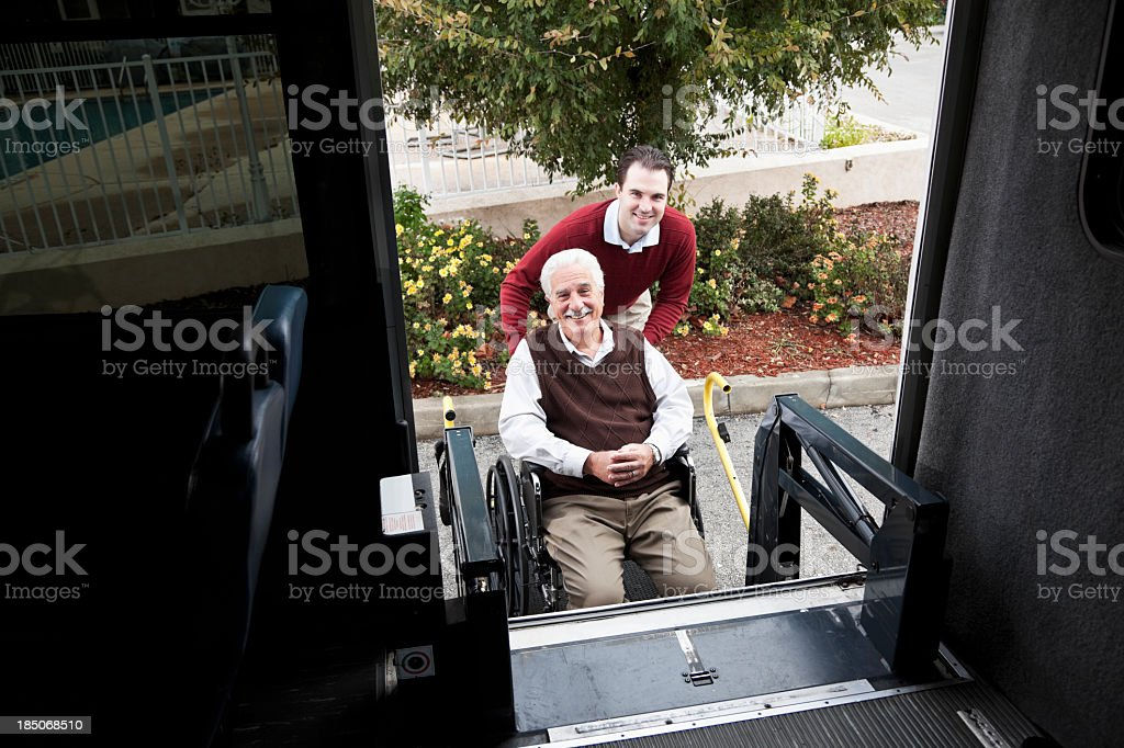 Senior man by minibus with wheelchair lift stock photo